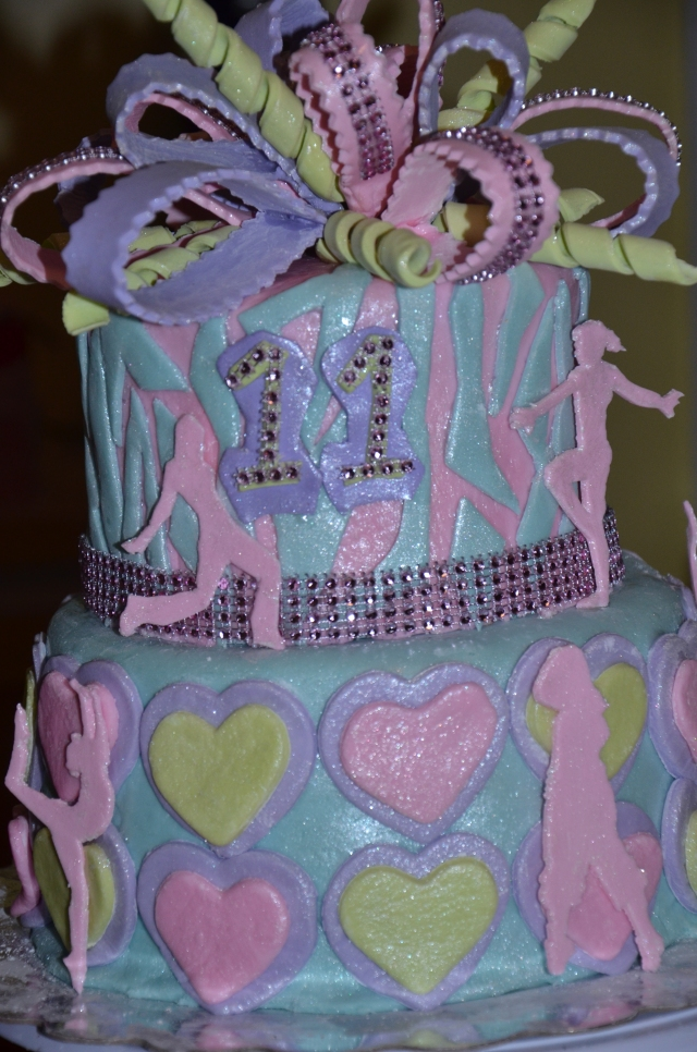 A By Grace Cakes birthday cake original. Gluten-free chocolate cake with vanilla buttercream. Covered with extra sparkles this cake displays hip hop and gymnastics silhouettes and a multiloop, multi-color bow.